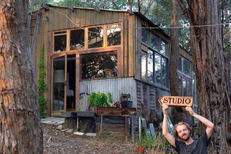 """Artek outside the studio holding a sign reading """"studio"""""""